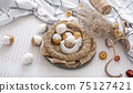 Easter composition with festive eggs in a decorative nest. 75127421