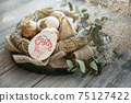 Easter composition with festive eggs in a decorative nest close up. 75127422