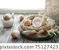 Easter composition with festive eggs in a decorative nest. 75127423