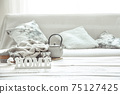 A teapot with hygge decor details and a decorative word home on the table in the living room. 75127425