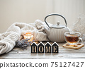 Cozy home composition with tea and decorative word home. 75127427
