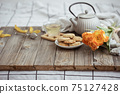 Spring home composition with a cup of tea, a teapot, cookies and a bouquet of flowers on a wooden surface. 75127428