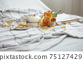 Spring home composition in bed with a cup of tea, cookies, a teapot, a book and a bouquet of flowers. 75127429