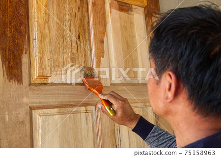 Painter Covering Lacquer Vanish on the Wooden Door in the Construction Work Site. 75158963