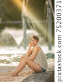 Half-beautiful woman sitting in the lagoon pool of Cairns 75200371
