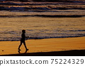 黃昏時分在沙灘上獨自行走的女孩(剪影) 75224329