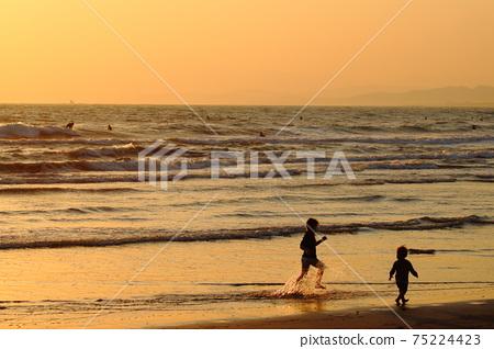 在黃昏時在沙灘上玩耍的孩子(剪影) 75224423