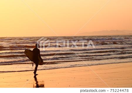 衝浪者(女性)黃昏時沿著海岸線走 75224478