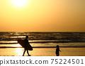 衝浪者和孩子們在黃昏時沿著海岸線走 75224501