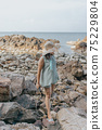 Beautiful woman walking on rock over sea 75229804