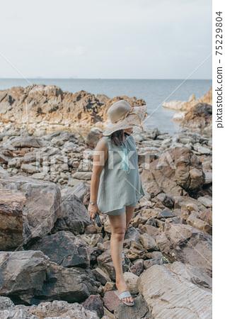 Beautiful woman walking on rock over sea 75229804