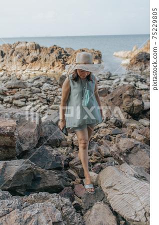 Beautiful woman walking on rock over sea 75229805