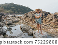 Beautiful woman walking on rock over sea 75229808