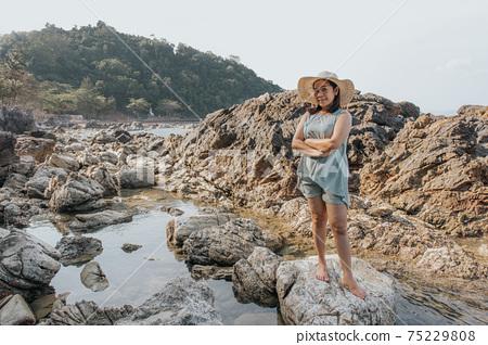 Beautiful woman walking on rock over sea 75229808