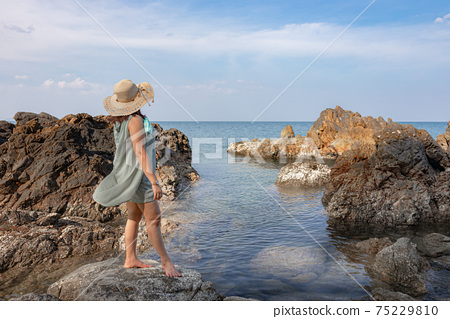 Beautiful woman walking on rock over sea 75229810