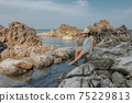 Beautiful woman walking on rock over sea 75229813