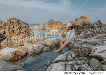 Beautiful woman walking on rock over sea 75229813