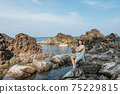 Beautiful woman walking on rock over sea 75229815