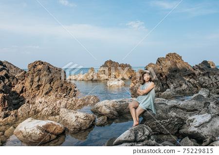 Beautiful woman walking on rock over sea 75229815