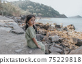 little girl sitting on rock over sea 75229818