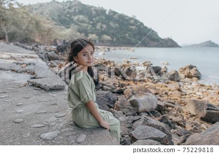 little girl sitting on rock over sea 75229818