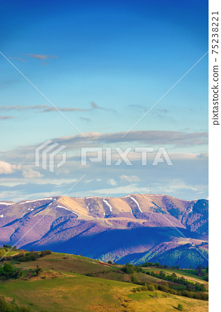 mountainous rural landscape in springtime. beautiful scenery beneath a sky with clouds. grass covered hill rolling in to the distant ridge 75238221