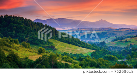 mountainous rural landscape at dawn. beautiful scenery with forests, hills and meadows in morning light. ridge with high peak in the distance. village in the distant valley 75268618