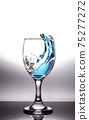 Splashing blue water into the crystal wine glass, closely spreading on a white background. 75277272