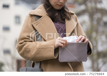Woman taking out a mask from the mask pouch 75279864