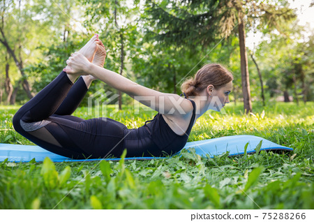 Beautiful woman doing Pilates in the green park 75288266