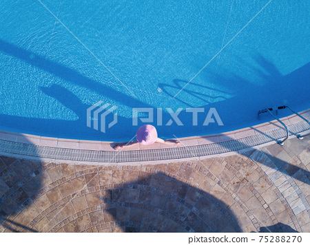 Young woman sunbathing in a swimming pool 75288270