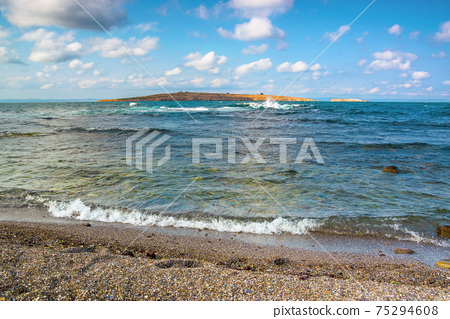 seascape with island in the distance. beautiful landscape of bulgaria near sozopol. waves crashing rocky shore. sunny weather with fluffy clouds on the sky 75294608