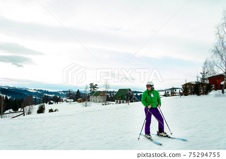Young man in green jacket and purple pants skiing. 75294755