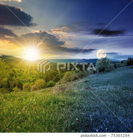 day and night equinox time change concept above mountainous countryside scenery in spring. trees and grass on hills rolling through green valley in to the distant ridge with sun and moon on the sky 75303284
