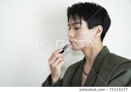 Men applying lipstick 75319157