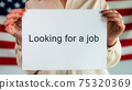 "A woman holds a poster that says ""looking for a job"". Standing in the background of the American flag 75320369"