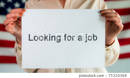 """A woman holds a poster that says """"looking for a job"""". Standing in the background of the American flag 75320369"""