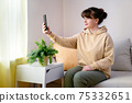 Young blone woman taking selfie at home 75332651