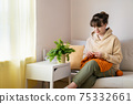 Young woman knitting orange knitwear on sofa at home 75332661