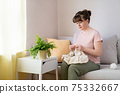 Young woman knitting white knitwear on sofa at home 75332667