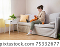 Young woman knitting on sofa at home 75332677