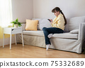 Young blonde woman sitting with smartphone on sofa 75332689