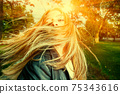 Young woman with wind swept hair backlit 75343616