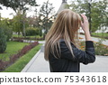 Blond haired outdoor fixed her hair. She wearing black leaser jacket. Side view. 75343618