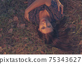 Top view of a gorgeous lady closed eyes and wearing ornate pattern dress posing on the grass with autumn leaves. Beautiful female with closed eyes has dreamy expression lying outdoor in the park 75343627