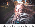 Long haired blonde is dancing in the park full of joy and happyness 75343634