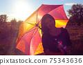 Girl smiling hiding under colorful umbrella 75343636