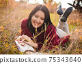 Young lady lying on the grass with poetry book 75343640