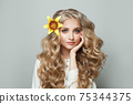 Attractive cheerful woman with healthy curly hair and yellow lily flower on white background 75344375