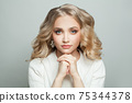 Beautiful woman with blonde hair and jewelry earrings on white background 75344378